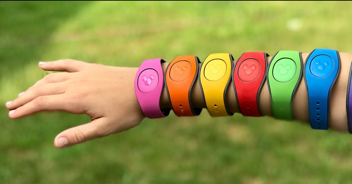An outstretched child's arm adorned with Disney's magic bands in every color of the rainbow.