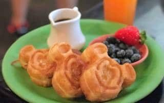 A plate with mini waffles in the shape of mickey with syrup and fresh fruit